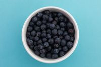 High angle view of bowl of blueberries on blue background
