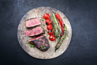 Barbecue dry aged wagyu roast beef steak with tomatoes and chili as top view on a rustic modern design plate with copy space