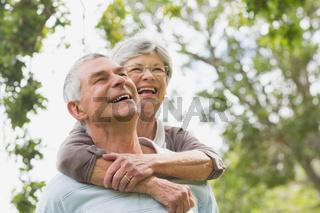 Senior woman embracing man from behind