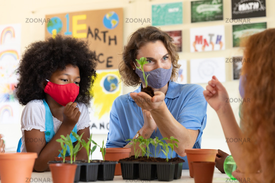 Female teacher wearing face mask showing plant pots to students in class