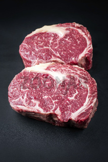 Raw dry aged wagyu entrecote beef steak as closeup on a black background with copy space