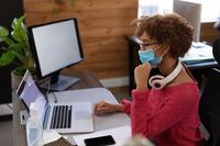 Mixed race woman wearing face mask using laptop at desk in casual office