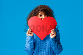 Cute and lovely flushed african-american girl, with afro haircut, in sweater, hiding face behind big red heart and peeking joyfully camera, confessing in love, sympathy, standing blue background