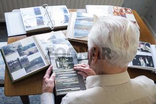 Senior man looking at photo albums.jpg