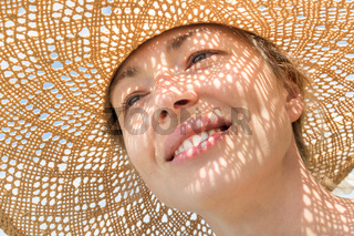Close-up portrait of woman wearing straw hat enjoying summer sun. Pattern of shadows falling on her face