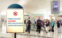 a sign inside an airport warns of the cancellation of flights form UK after new Covid-19 variant discover