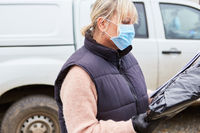 Paketbotin eines Lieferdienst mit Mundschutz überprüft Lieferung