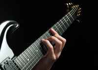 guitarist hand playing guitar over black