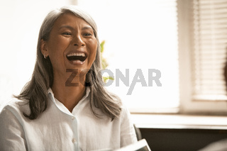 Funny Asian business woman laughing at business meeting. Gray haired senior lady have fun in office. Close up portrait. Toned image
