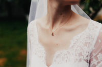 Gold pendant around neck of bride in a white dress with veil. Blurred background