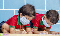 Kids busy in writing with medical face mask wearing due to covid-19 or coronavirus outbreak or pandemic at school - children painting at home during lockdown.