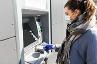 woman in medical mask and glove with money at atm