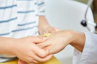 Kind klebt Pflaster auf Hand von der Kinderärztin