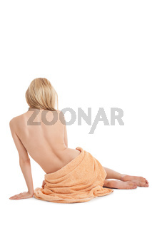 young blonde woman sitting on towel naked back isolated