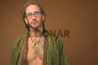 Young handsome Hispanic man with dreadlocks against brown background