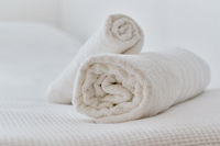 Folded white towels on bed, close up view