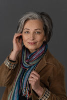 Stylish graying Woman charmingly smiles looking at camera. Caucasian mid aged beauty dressed in brown corduroy jacket with multi-colored scarf touches her face with hand. Anti-aging skin care concept