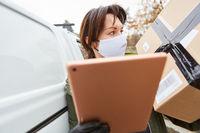 Lieferdienst Paketbotin stellt Lieferung mit Tablet zu