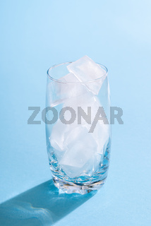 Glass with ice cubes on blue background. Empty glass with ice