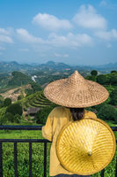 Beautiful closeup of a female leaning on the fences in Asian conical hat against mountains