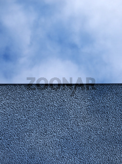 a pane of shattered glass with straight edge dividing the image against a blue cloudy sky