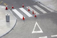 Road painting maintenance concept. Painting white street lines on pedestrian crossing and road cones on city