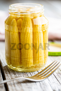 Pickled young baby corn cobs in jar.