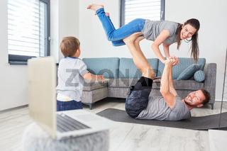 Eltern turnen im Wohnzimmer mit Kleinkind