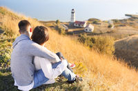 Romantic couple dressed in cozy sweaters together near the lighthouse