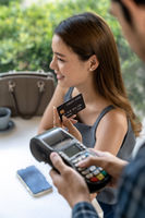 Asian customer make payment with contactless credit card.