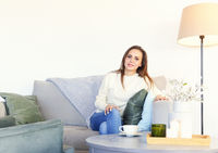 Relaxed woman sitting on sofa at home