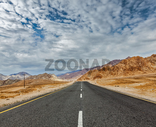 Travel forward concept background - road in Himalayas with mountains and dramatic clouds. Ladakh