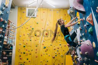 Young woman climbing a tall, indoor, man-made rock climbing wall