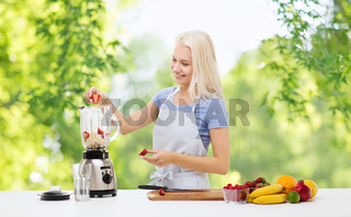 smiling woman with blender making fruit smoothie