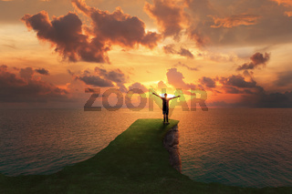Solo man traveler adventurer standing on the top edge of a rock cliff watching a sunset over sea