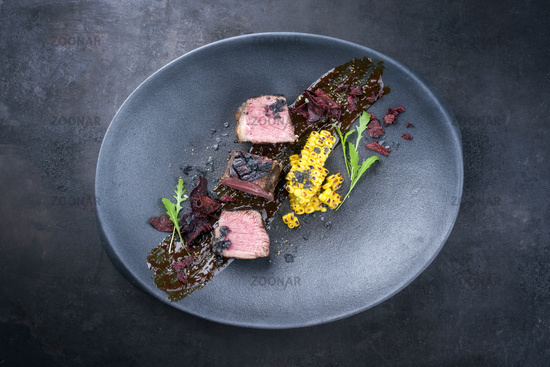 Modern style barbecue dry aged wagyu roast beef steak with corn and vegetable chips on spicy sauce offered as top view on a design plate