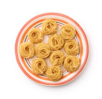 Top view of plate with uncooked tagliolini pasta nests