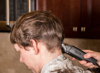 Caucasian man having hair cut in kitchen with towel around his shoulders