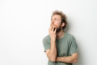 Pensive scratching beard young man with hands folded. Handsome young man with curly hair in olive t-shirt looking up away isolated on white background