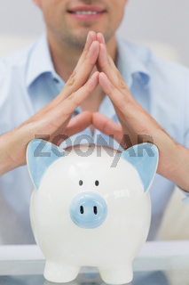 Close-up mid section man with piggy bank at home
