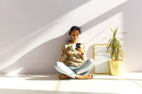 Ethnic woman with cup of coffee using smartphone at home