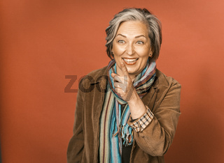Cheerful creative woman laughs pointing finger at something. Happy mature model wearing casual style posing on orange background. Tinted image