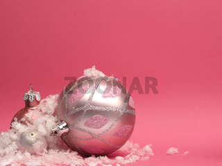Pink vintage Christmas baubles on a pink background with space for your text or image