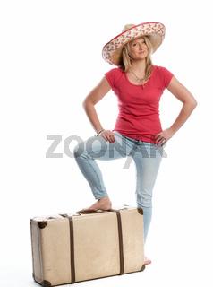 frau mit reisekoffer trägt einen sombrero