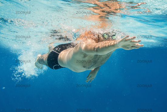 Pro male swimmer in the blue water