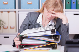 Overwhelmed woman at the office. Overworked