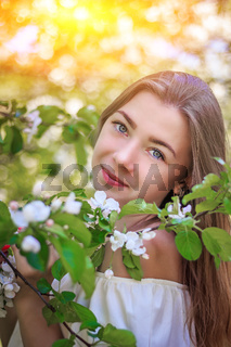 Portrait of a girl in a flowering Apple tree . A beautiful girl looks into the frame. Smile. Fair-haired girl. The flowering tree. Portrait
