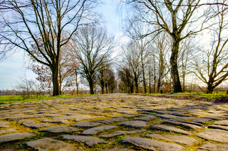 Road paved with paving stones. Old cobblestone way in perspective without cars.