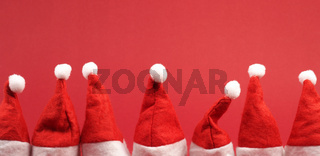 Hat of Santa in a row on red