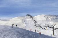 Snowy ski track prepared by snowcat, chair-lift, skiers and snowboarders in ski resort